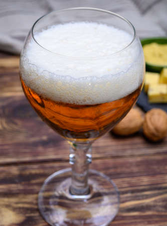 Glass of Belgian abbey blond beer and stone plate with cheeses made by monks from cow milk with fenugreek and mustard seeds close up