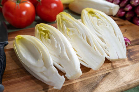 Fresh Belgian endive or chicory bitter salad ready to cook or eat close up