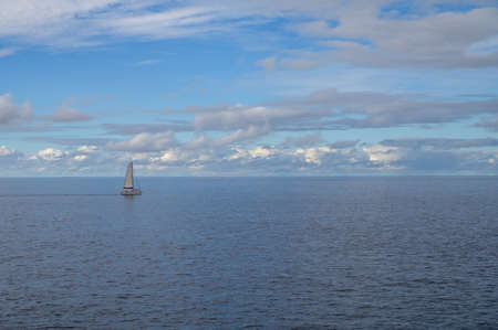 Seascape with one small sail boat, cloudy sky and waves of Atlantic ocean