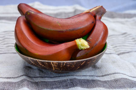 Bunch of ripe red bananas close up in bowl