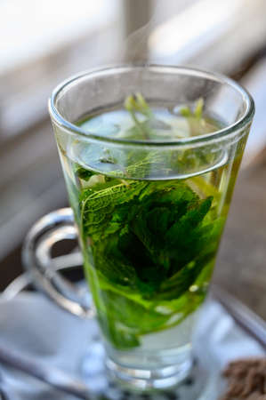 Tea glass with hot mint tea made fron fresh green leaves of  mint plant close up
