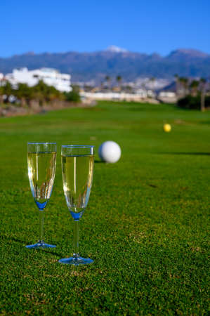 Excellent well-kept green grass lawn on large golf course, green section with big white foam balls for beginners on Tenerife island, Canary, Spain close up and two glasses with Spanish cava wine
