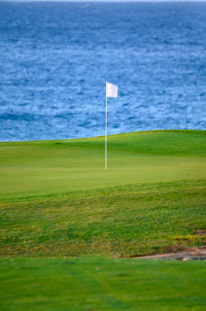 View on evergreen grass field with white pin on large golf course and blue Atlantic ocean on Tenerife island, Canary, Spain on sunrise