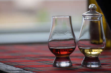 Special tulip-shaped glass with lid for tasting of Scotch whisky on distillery in Scotland, UK and red tartan