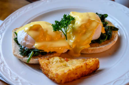 Weekend vegetarian breakfast in Scotland with two eggs benedict on homemade muffuns with spinach and yellow hollandaise sauce.