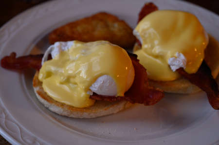 Weekend breakfast in Scotland with two eggs benedict on homemade muffuns with roasted bacon and yellow hollandaise sauce.