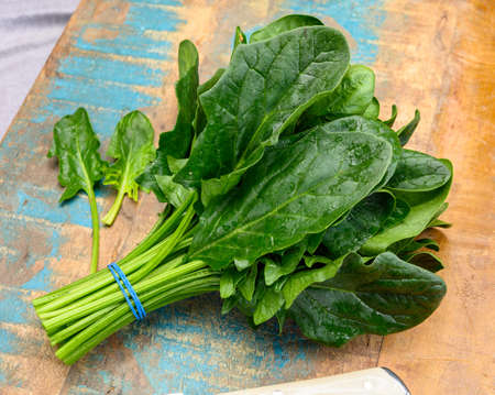 Bunch of young fresh leaves of dietary green organic spinach ready to cook Reklamní fotografie