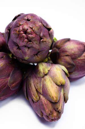 Heads of raw fresh purple romanesco artichoke vegetable ready to cook