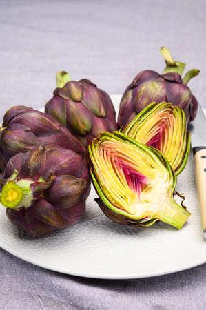 Heads of raw fresh purple romanesco artichoke vegetable ready to cook on white board Reklamní fotografie
