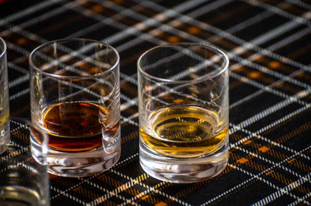 Special tumbler glasses for Scotch whisky, tasting tour on distillery in Scotland, UK and dark tartan close up