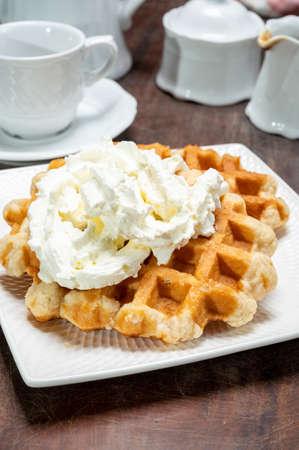 Tasty Belgian dessert, Brussels sugar waffles with  whipped cream close up Reklamní fotografie
