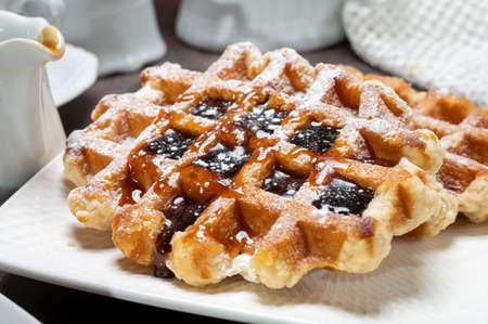 Tasty Belgian dessert, Brussels waffles with syrup and white sugar powder close up Reklamní fotografie