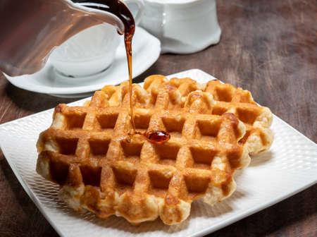 Tasty Belgian dessert, homemade Brussels sugar waffles with dark syrup close up Reklamní fotografie