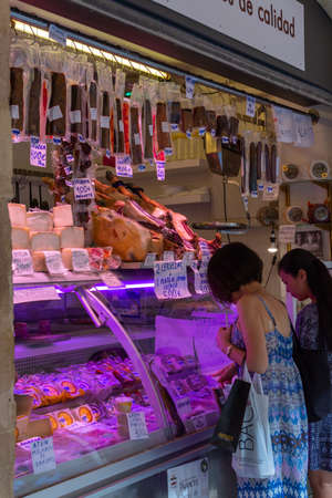 September 2, 2019, Cadiz, Andalusia, Spain, Chinese tourists in Europe, daily farmers market, different ham jamon serrano legs, cheese and sausages to sell by local people Editorial