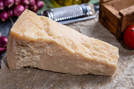One piece of authentic Parmigiano-Reggiano or Parmesan Italian hard, granular cheese close up
