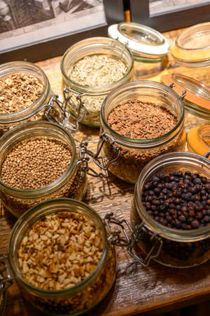 Tastes of gin, botanicals ingredients for gin distillery process, dried orange peels, juniper berries, heather, angelica, coriander, clove, cassia, liquorice in glass pots
