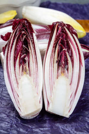 Fresh organic Belgian endivi or green and red chicory lettuce close up in violet protective paper