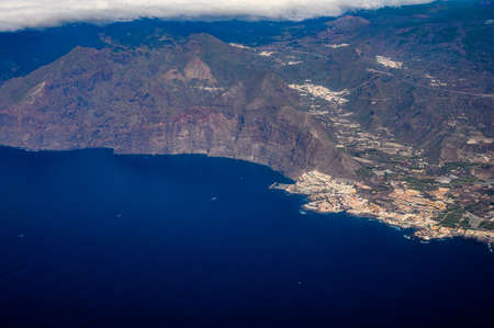 Aerial overcloud view on Tenerife island from airplane, Los Gigantes village Stock Photo