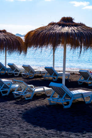 Thatched parasols and chairs on black voulcatic lava sand beach