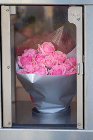 Self-service flowers vending machine, show window with pink roses close up