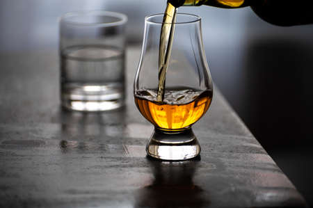 Pouring in tulip-shaped tasting glass Scotch single malt or blended whisky and glas of water