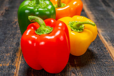 Fresh red, orange, green and yellow sweet bell paprika close up