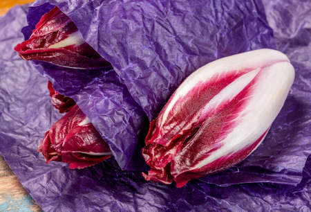 Fresh organic Belgian endivi or red chicory lettuce close up in violet protective paper Banque d'images