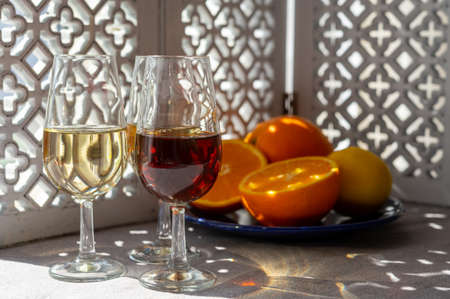 Glasses with cold fino sherry fortified wine and orange in summer sunlights, andalusian style interior on background Stock Photo