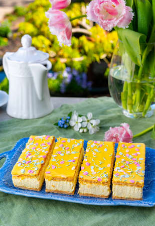 Four tompouce cakes with whipped cream and yellow icing served in sunny spring garden
