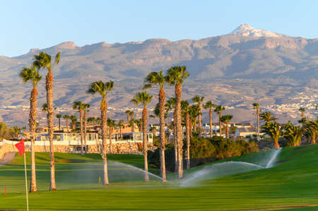 Watering of evergreen grass field on large golf course and view on Mount Teide, Tenerife island, Canary, Spain on sunrise