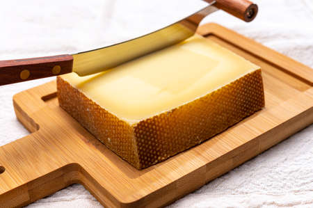 Block of Swiss medium-hard matured cheese gruyere used for baking, quiche, fondue, sandwiches close up