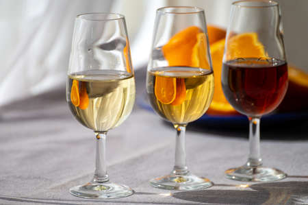 Glasses with cold dry fino and sweet cream sherry fortified wine in summer sunlights, andalusian style interior on background Reklamní fotografie