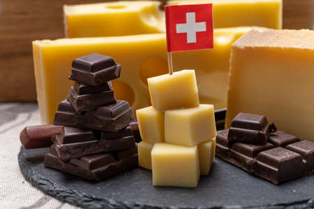 Tasty Swiss food, block of medium-hard yellow cheese emmental or emmentaler with round holes, matured gruyere and high quality milk chocolate close up served in cubes as mountains top with Swiss flag. Stockfoto