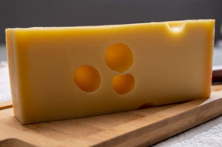 Block of Swiss medium-hard yellow cheese emmental or emmentaler with round holes close up Stock Photo