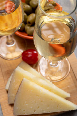 Glasses of dry cold fino sherry wine served with spanish tapas, manchego cheese, green olives, cheese crackers
