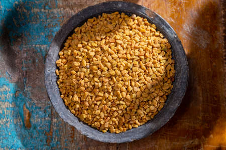 Indian spices collection, dried aromatic fenugreek seeds and another spices in clay bowls close up