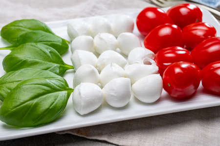 Italian food served as flag of Italy Tricolore with fresh fresh green basil, white mini mozzarella cheese and red cherry tomatoes close up