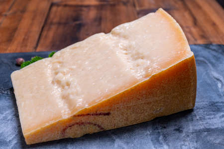 Big wedge of parmigiano-reggiano parmesan hard Italian cheese made from cow milk or Grana Padano  close up