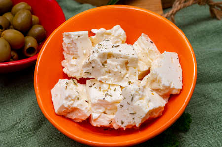 Ingredient for traditional Greek salad, fresh white salted feta cheese with herbs Imagens