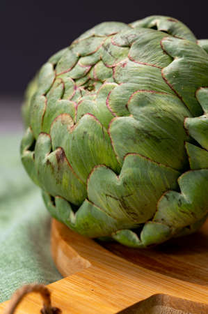 Big ripe uncooked green globe artichoks vegetables close up Imagens