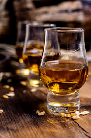 Small tasting glasses with aged Scotch whisky on old dark wooden vintage table with barley grains close up