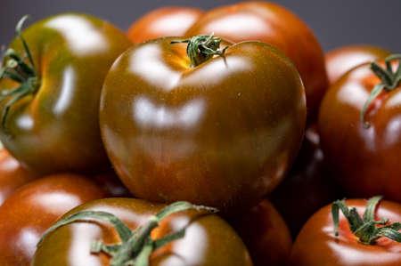 Fresh ripe sweet reddish brown and green kumato tomatoes close up