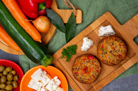 Tasty organic vegetarian food, burgers with Greek feta cheese, sweet red paprika, green olives and zucchini Imagens