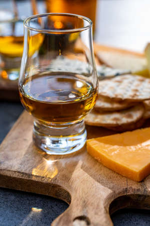 Whiskey and cheese pairing, tasting whisky glasses and plate with sliced cheeses close up Фото со стока