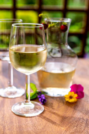 Summer tasting of cold white grape wine on sunny garden terrace with wooden pergola