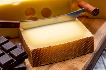 Tasty Swiss food, block of medium-hard yellow cheese emmental or emmentaler with round holes, matured gruyere and high quality milk chocolate close up Stock fotó