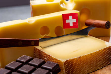 Tasty Swiss food, block of medium-hard yellow cheese emmental or emmentaler with round holes, matured gruyere and high quality milk chocolate close up