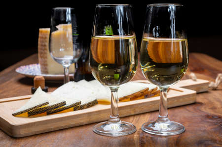 Spanish fino dry sherry wine from Andalusia and pieces of different sheep hard manchego cheeses made in La Mancha, Spain. Wine and cheese pairing