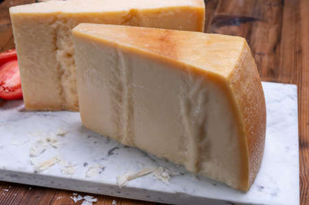 Big wedges of parmigiano-reggiano parmesan hard Italian cheese made from cow milk or Grana Padano close up