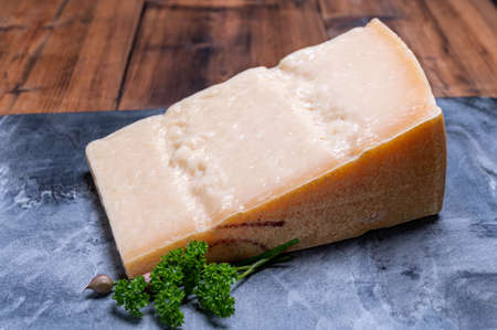 Big wedge of parmigiano-reggiano parmesan hard Italian cheese made from cow milk or Grana Padano close up Stock Photo
